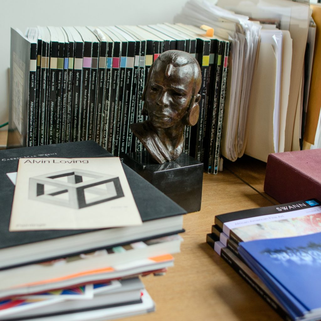 A bust sculpture by Elizabeth Catlett surrounded by auction catalogues and books.
