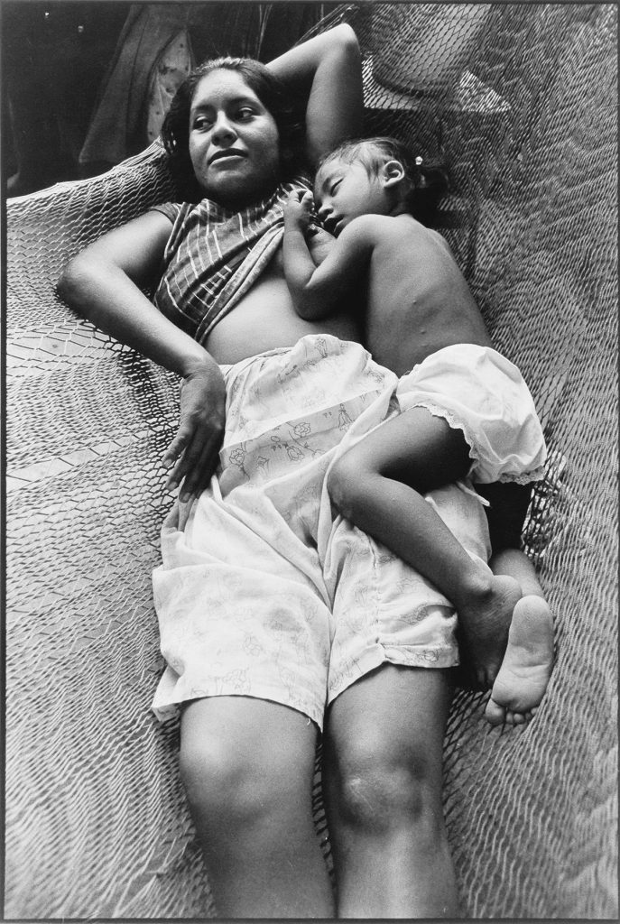 Black and white photograph of a mother and child in a hammock by Graciela Iturbide