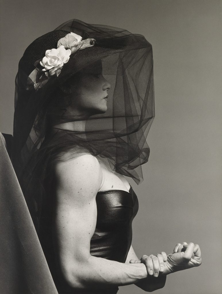 Black and white photograph of a veiled Lisa Lyon flexing her right arm by Robert Mapplethorpe.
