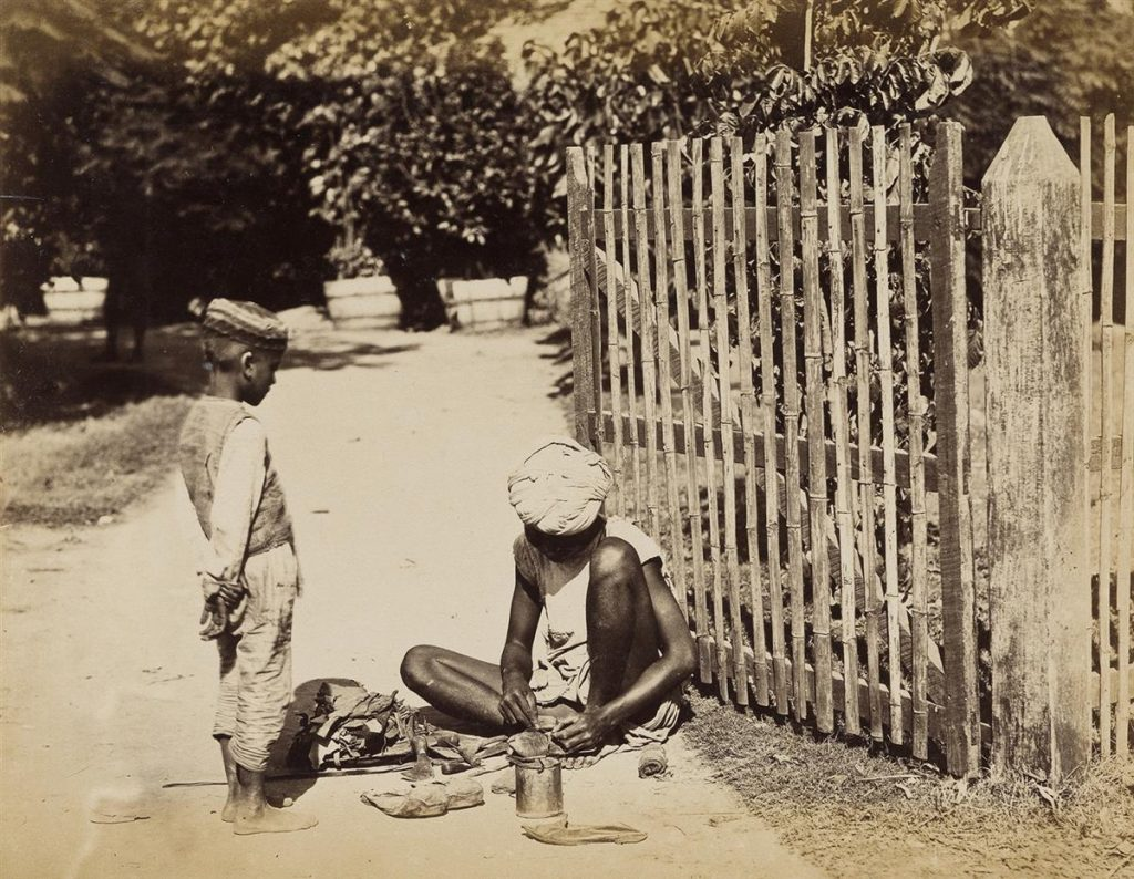 Image of a young Indian boy and teen sitting on the streets of India in the 1870s.