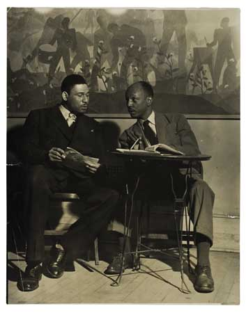 Black and white photograph of Frederick O'Neal & Abram Hill seated in front of Aaron Douglas's mural at the Schomburg Center for Research in Black Culture, circa 1940-45.